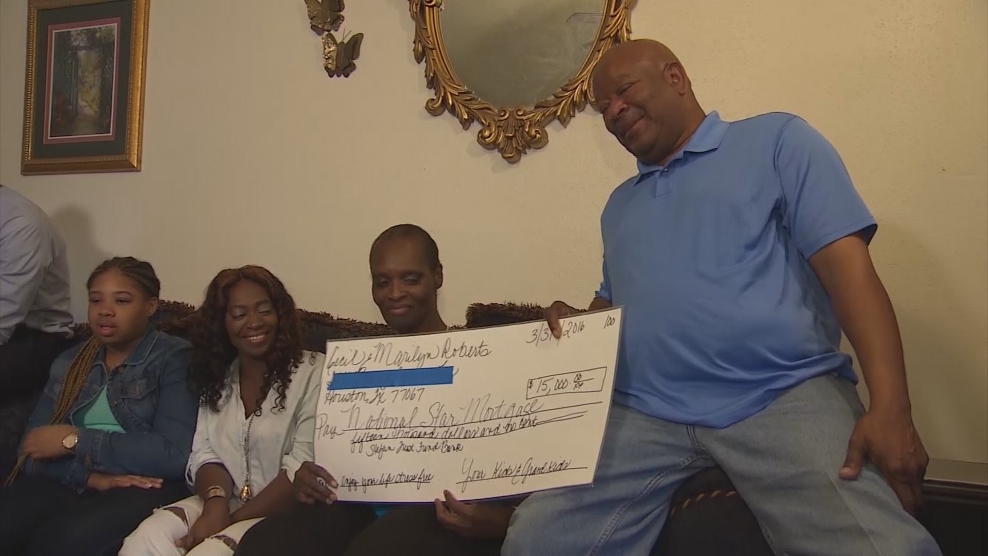 Cecil and Marilyn Roberts hold the check Stefun presented them to pay off their mortgage.   (Photo: KHOU)